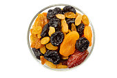 Glass bowl of dried fruits mix isolated on white background. Top view