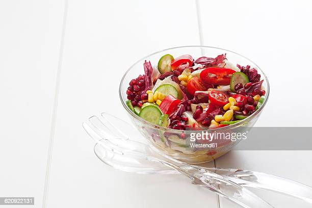 Glass bowl of mixed salad on white ground