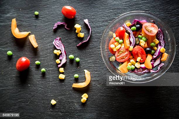 Glass bowl with mixed salad and different raw vegetables on slate