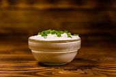 Glass bowl with sour cream and chopped green onion on rustic wooden table