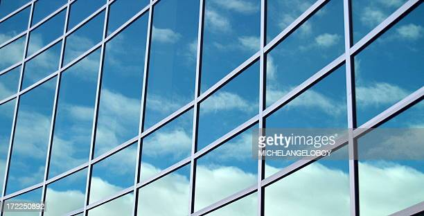 Glass building reflecting blue skies and clouds