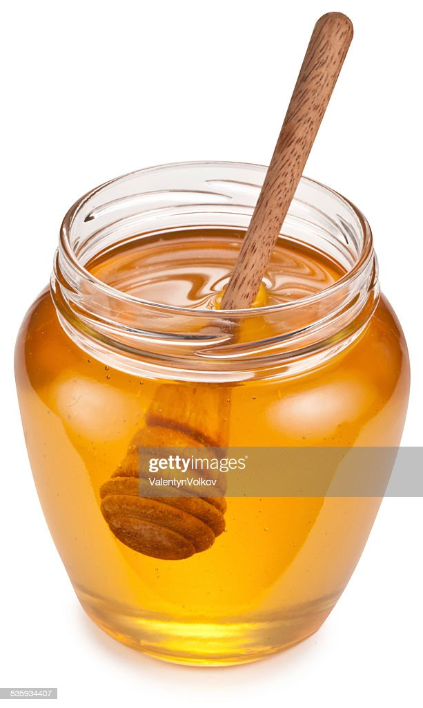 Glass can full of honey and wooden stick in it. : Stock Photo