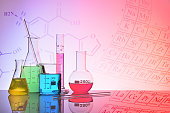 Laboratory glass chemical containers on glass table isolated colorful with representation background. Horizontal composition. Front view