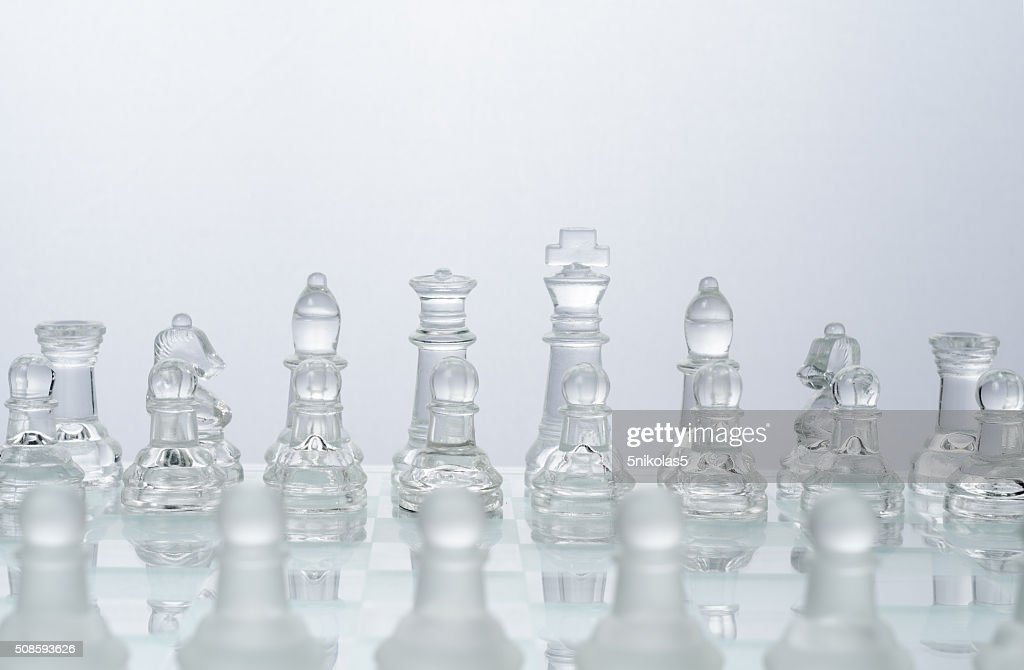 glass chess on the transparent chessboard : Stock Photo
