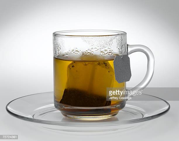 Glass cup and saucer holding tea bag and water, close-up
