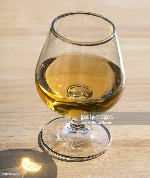 Glass cup filled with whiskey on a wooden table illuminated by sunlight
