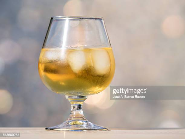 Glass cup filled with whiskey with ice on a wooden table illuminated by sunlight