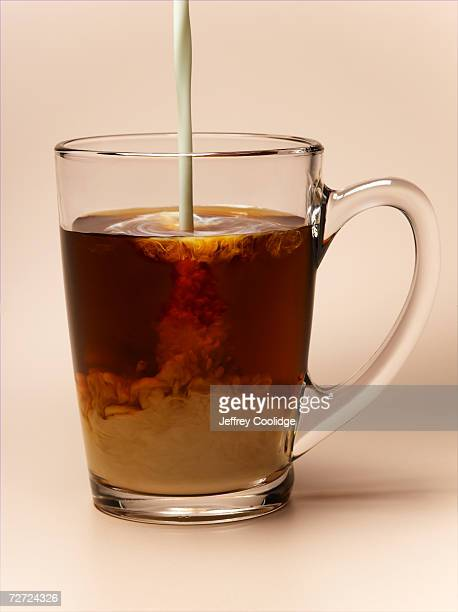 Glass cup holding coffee with milk pouring in, close-up