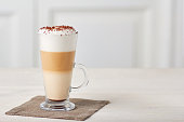 Glass cup of coffee latte on textile napkin over white wooden table