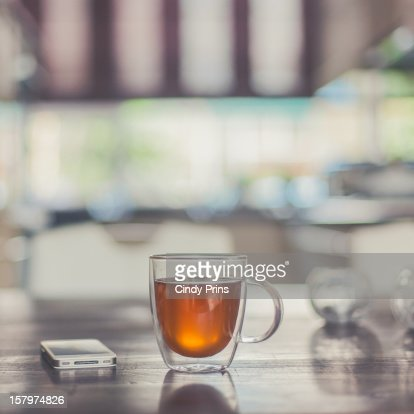 A glass cup of tea and a mobile phone on a table