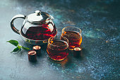 Two glass cups and teapot with black tea and chocolate candies on dark background.