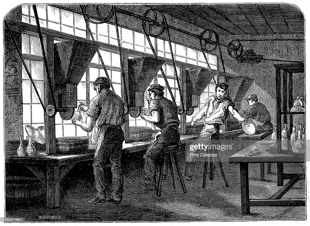 Glass cutters at their wheels, c1870. The vessel to be cut is held against a rotating wheel powered by steam through belt and shafting.