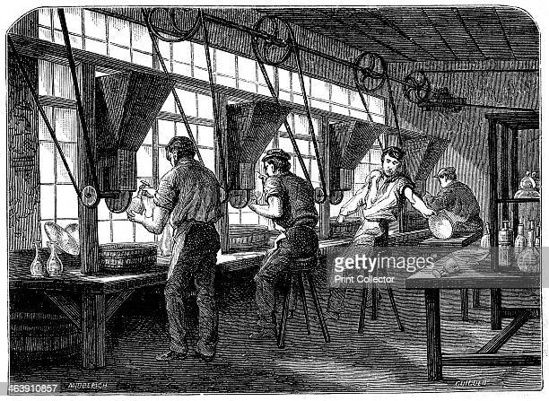 Glass cutters at their wheels c1870 The vessel to be cut is held against a rotating wheel powered by steam through belt and shafting