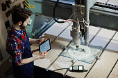 Factory worker operating cutter machine using digital tablet in workshop