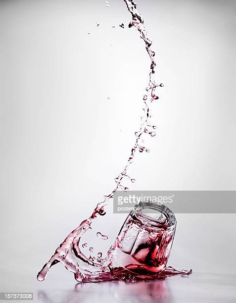 A glass falling with red liquid