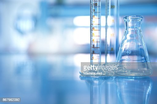 glass flask with cylinder in blue science laboratory background : Stock Photo