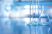 glass flask with measurement cylinder in blue science laboratory background