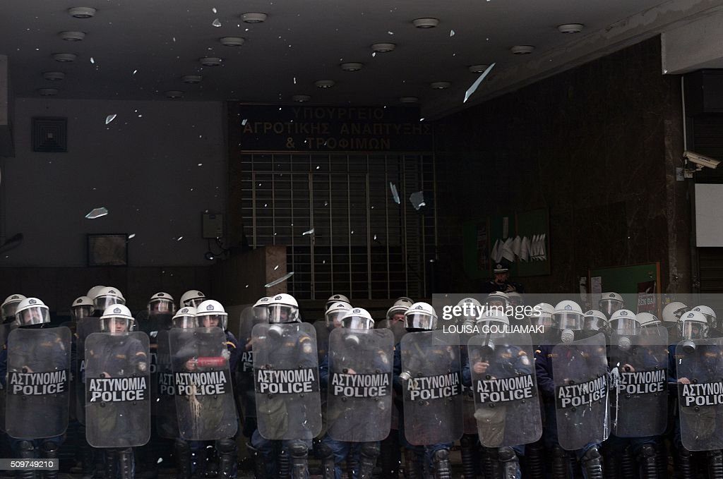 Glass from ministry's broken windows falls in front of police officers in Athens during a demonstration of farmers against the pension reform on February 12, 2016. Fears that Greece will exit the eurozone, a 'Grexit', could revive if Greek authorities do not come up with 'credible' reforms, notably on pensions, a senior IMF official said February 11, 2016. / AFP / LOUISA GOULIAMAKI