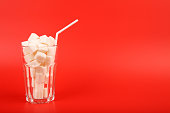 Glass full of sugar cubes isolated on red background - unhealthy diet concept