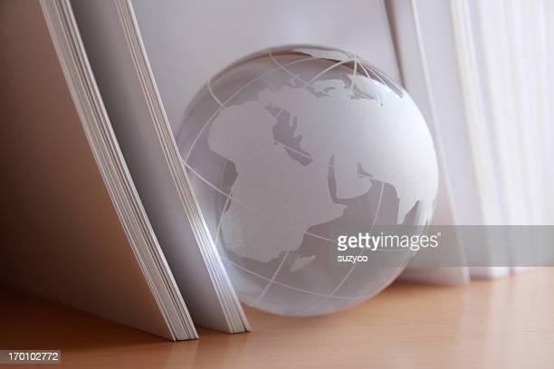 glass globe among book sheets