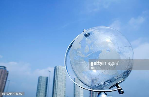 Glass globe in front of city skyline, low angle view