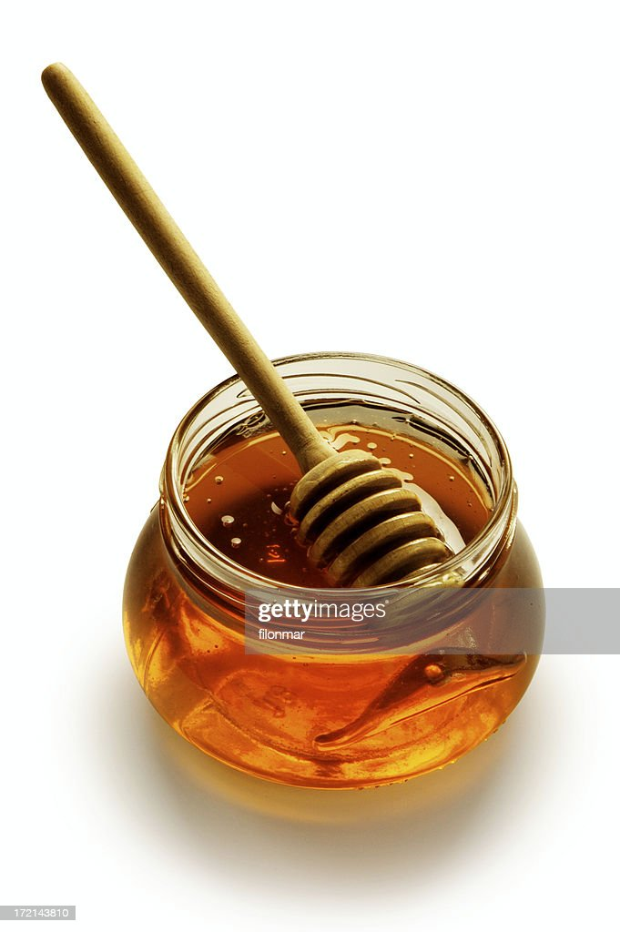 Glass honey pot with stick isolated on white background
