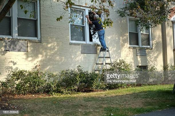 A glass installer puts a plexiglass pane over Miriam Carey's window in Stamford CT on October 4 2013