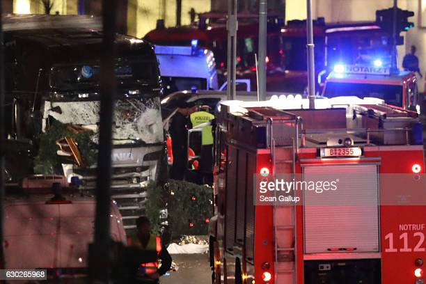 Glass is shattered on the windshield as workers and security inspect the damaged lorry truck after it was ploughed through a Christmas market on...