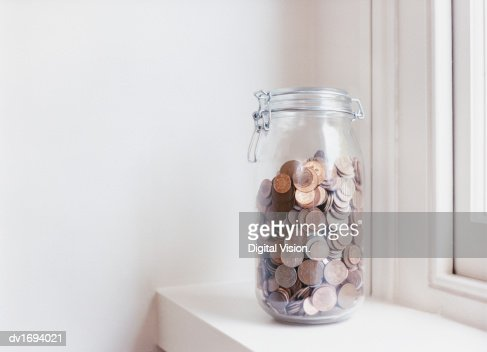 Glass Jar Filled with Coins on a Windowsill : Stock Photo