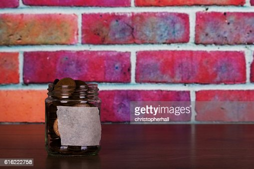 Glass jar on wooden surface filled with old coins : Stock Photo