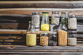 Few Seeds, Grain and Cereals in Glass Jars with Wooden Background