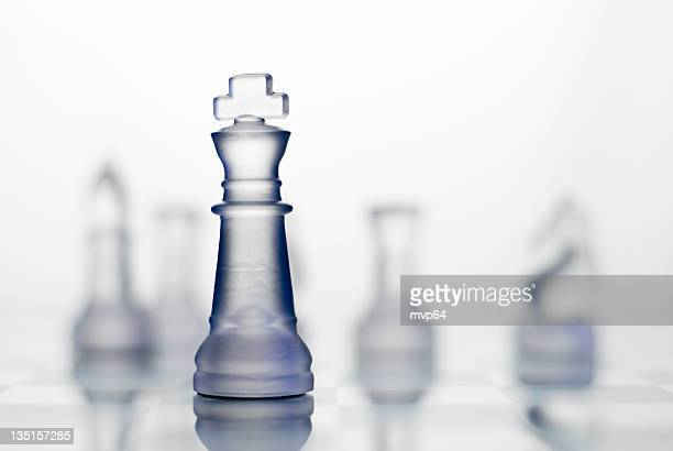 Glass king chess piece with blurred view of other pieces