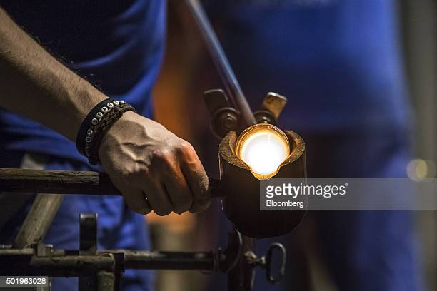 A glass maker shapes a ball of molten glass on the end of a blow pipe using a wooden mold in the melting house at the Novosad Son Glassworks in...