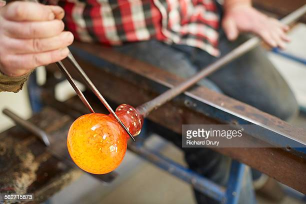 Glass maker shaping hot glass