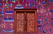 A glass mural surrounds a beautifully carved window on the wall of Wat Xieng Thong, Luang Prabang