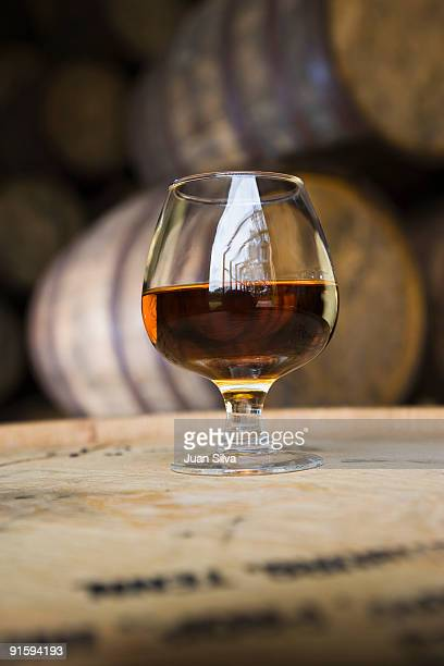 Glass of 12 years rum of on barrel.