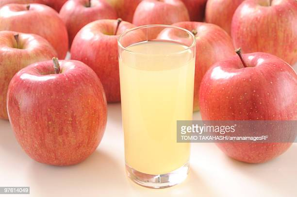Glass of apple juice amongst apples