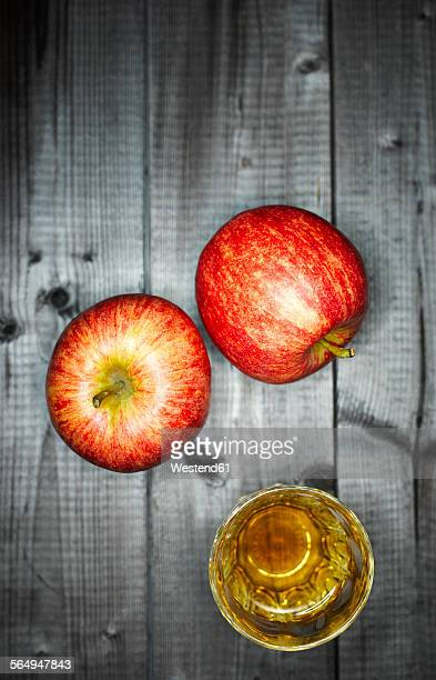 Glass of apple juice and two apples on wood