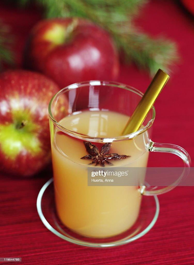 Glass of apple juice with two apples