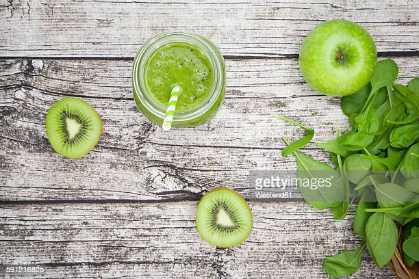 Glass of apple kiwi spinach smoothie and ingredients