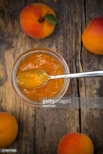 Glass of apricots jam and apricots on wood, elevated view