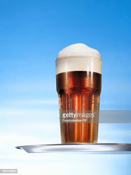 Glass of beer on tray, close up
