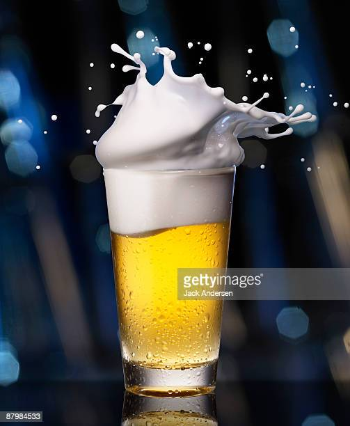 Glass of beer with splashing foam