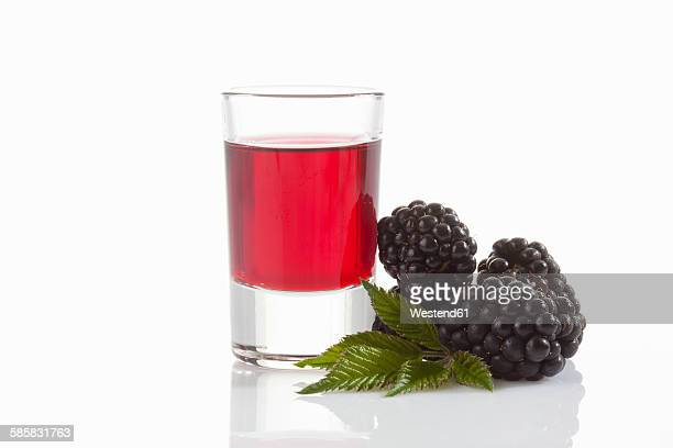 Glass of blackberry liqueur, blackberries and leaves on white ground