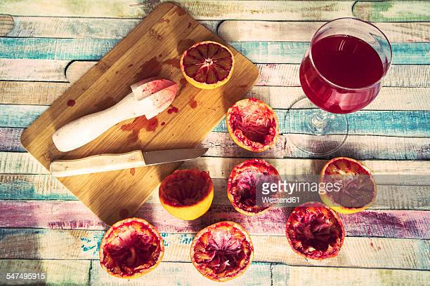 Glass of blood orange juice, squeezed blood oranges and juice squeezer