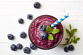 Glass of blueberry smoothie on white wooden background from top view