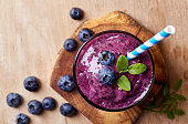 Glass of blueberry smoothie on wooden background from top view