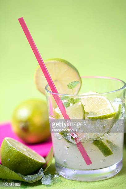 Glass of caipirinha with lime and straw