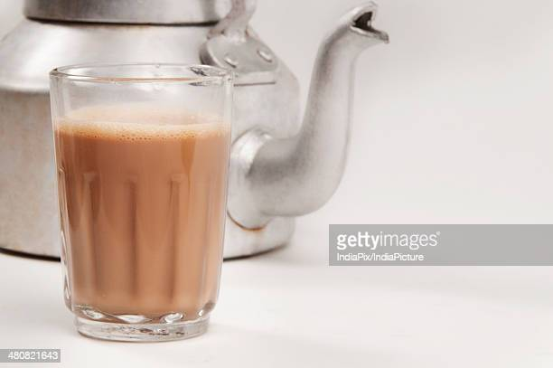 Glass of chai with an old fashioned kettle isolated over white background