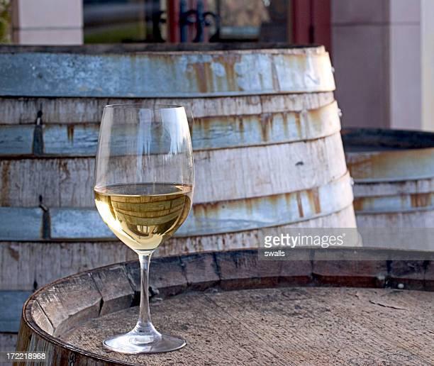 A glass of Chardonnay sitting on a barrel